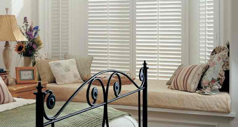 Plantation shutters in a chic bedroom bay window.