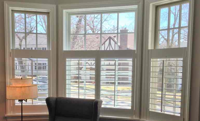 Half plantation shutters in living room bay window.