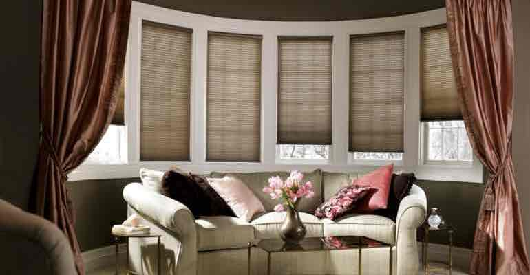 Brown cellular shades in living room bow window.