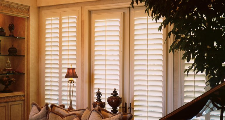Plantation shutters on windows and door in Sacramento parlor