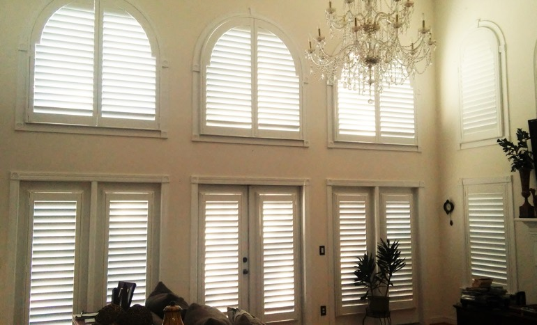Family room in two-story Sacramento home with plantation shutters on high windows.
