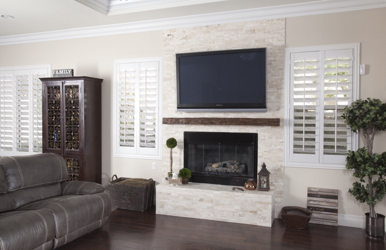 White plantation shutters in a Sacramento living room with solid hardwood floors.