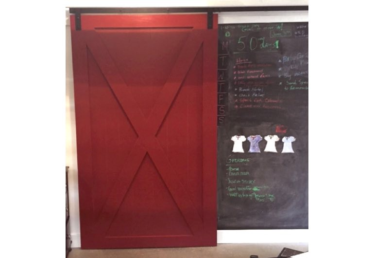 Bright red barn door with black track next to chalkboard 🚪