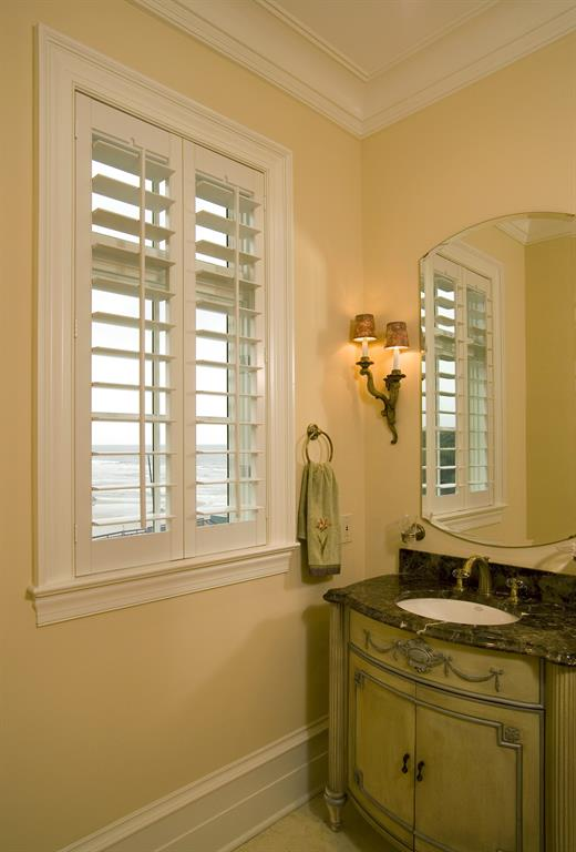 White plantation shutters in a bathroom looking out over ocean