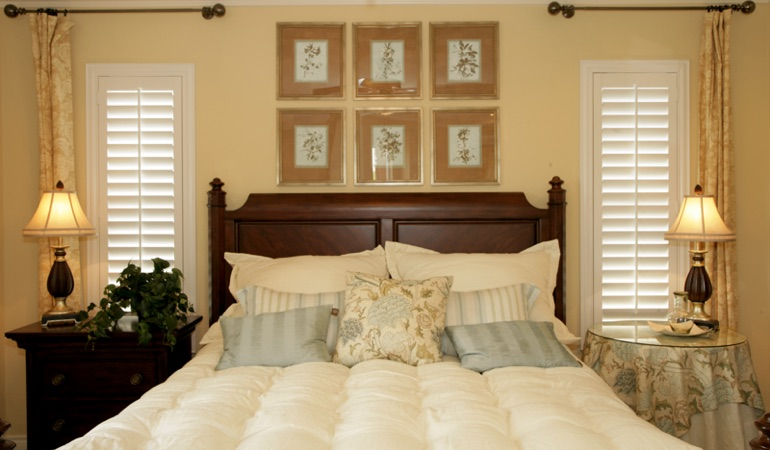Bedroom with two tall plantation shutters on either side of bed in Sacramento